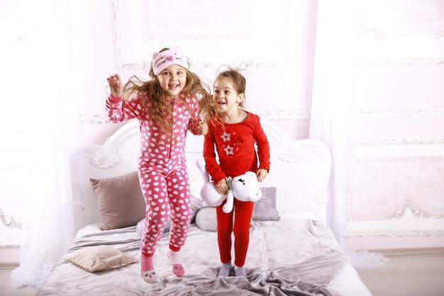 Crianças engraçadas felizes, vestidas com pijamas brilhantes estão pulando na cama e brincando juntos