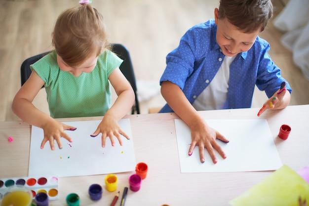 Crianças engraçadas mostram as palmas das mãos a tinta pintada.