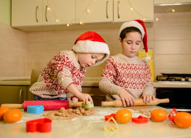 Crianças engraçadas preparam comida de férias para a família. chefs de papai noel. natal