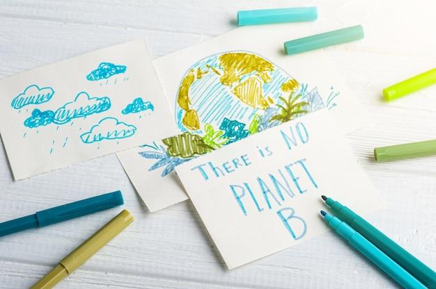 Crianças entregam desenho da terra na mesa branca com marcadores azuis e verdes.