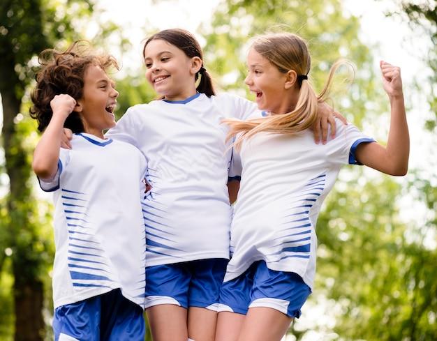 Crianças entusiasmadas depois de vencerem uma partida de futebol
