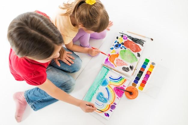 Crianças entusiasticamente pintam com aquarelas