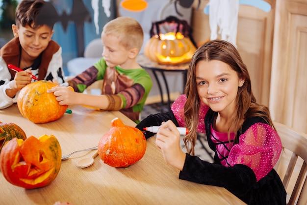 Crianças envolvidas. três crianças se sentindo envolvidas na decoração de abóboras para a festa de halloween em seu jardim de infância