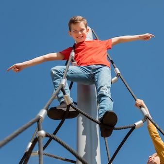 Crianças escalando corda juntas de perto