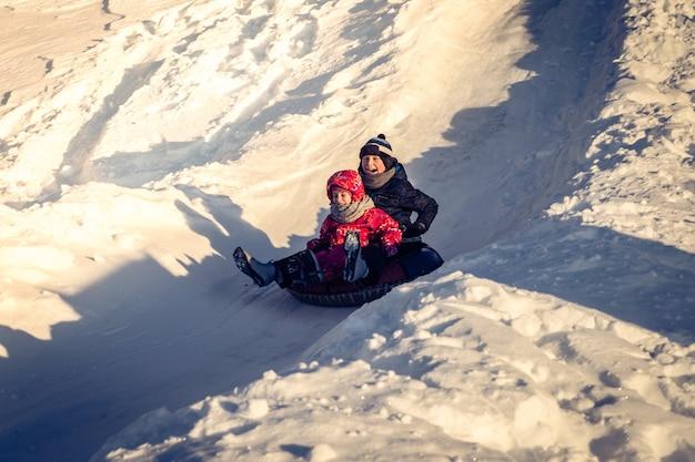 Crianças escorregando em tubos de neve