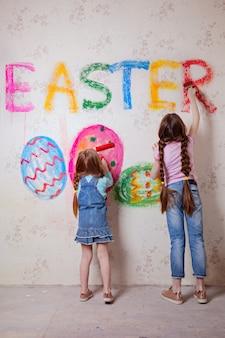 Crianças escrevem na parede a palavra páscoa