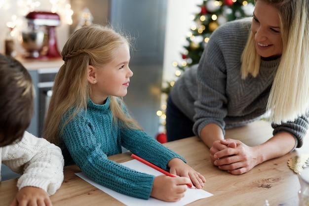 Crianças escrevendo desejos de presentes para o papai noel
