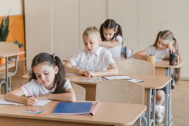 Crianças escrevendo em cadernos durante as aulas