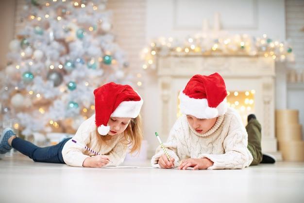 Crianças escrevendo uma lista de desejos no chão com uma decoração de natal no fundo