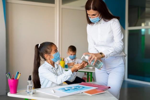 Crianças esperando para desinfetar as mãos na aula