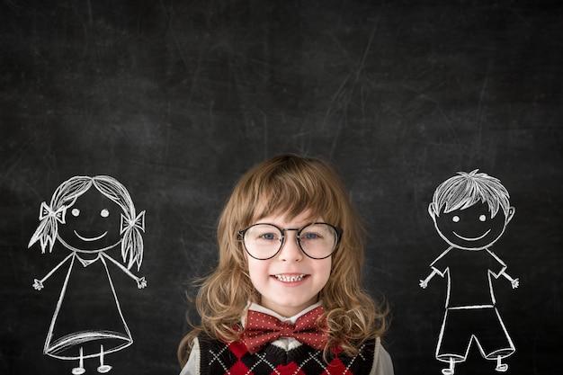 Crianças espertas na sala de aula. crianças felizes contra o quadro-negro. conceito de educação