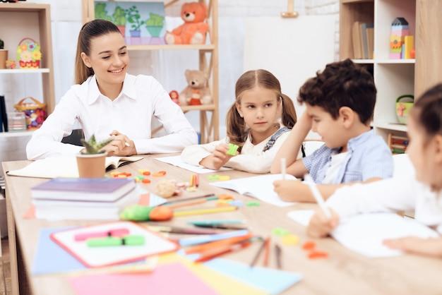 Crianças estudam cartas em sala de aula na escola.
