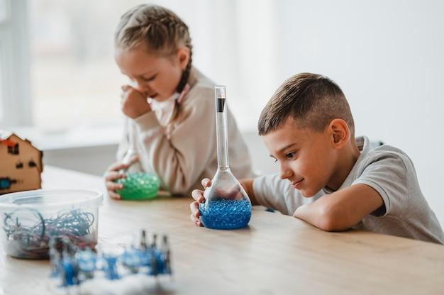 Crianças estudando química na aula com diferentes elementos