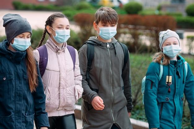 Crianças estudantes com máscaras médicas deixam a escola