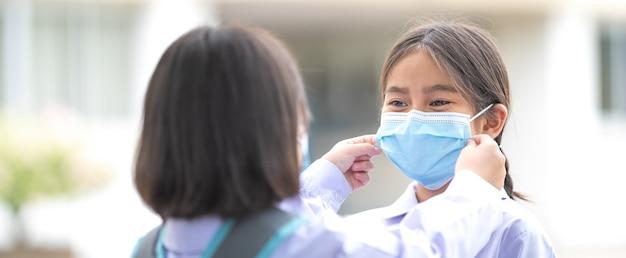Crianças estudantes em uniforme de estudante usando máscara protetora para o outro irem para a escola depois que a situação de pandemia do covid-19 está melhorando. de volta ao conceito de escola stock photo