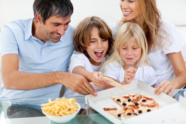 Crianças excitadas comendo uma pizza com seus pais