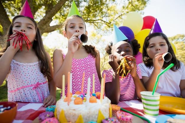 Crianças expirando em um trompete de aniversário durante uma festa de aniversário