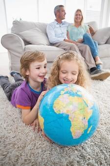 Crianças explorando o globo enquanto os pais estão sentados no sofá