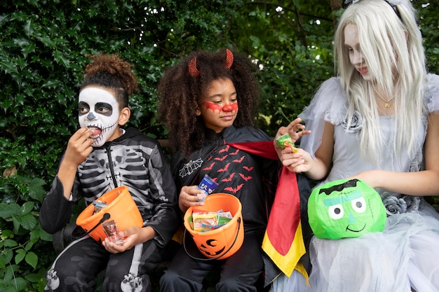 Crianças fantasiadas comendo seus doces