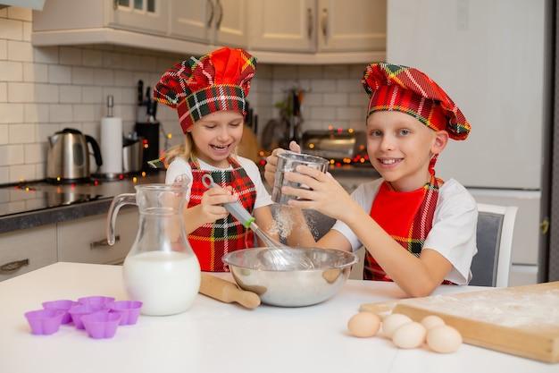 Crianças fantasiadas de chef preparam massa com farinha, leite, ovos e manteiga para os doces de natal