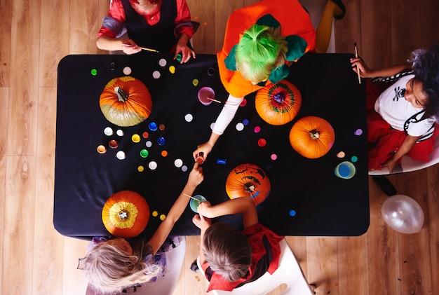 Crianças fantasiadas decorando uma abóbora