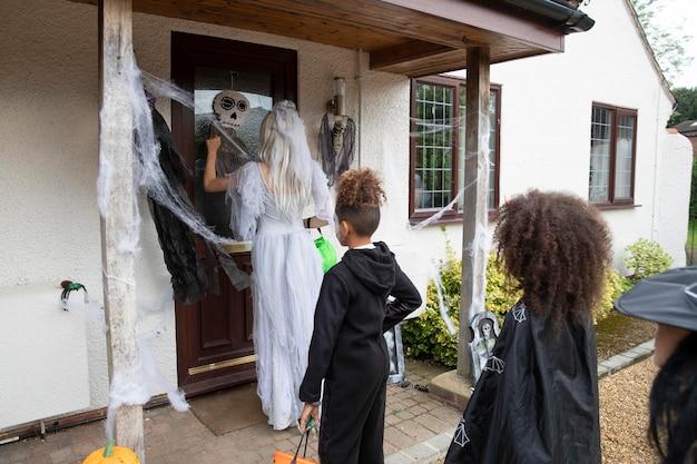 Crianças fantasiadas fazendo truques ou travessuras na casa de alguém