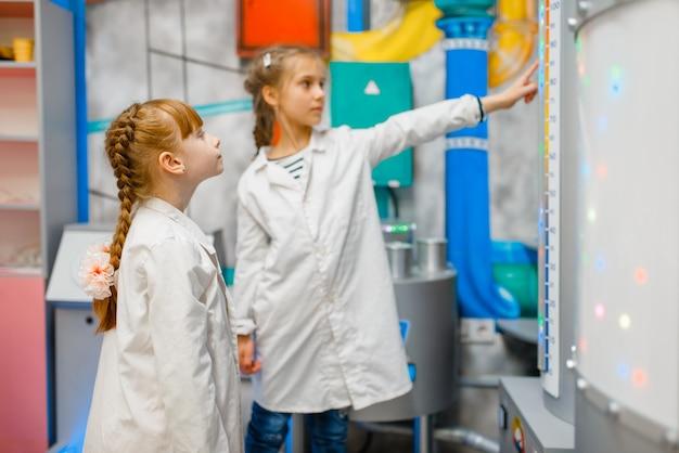 Crianças fardadas brincando de médico em laboratório