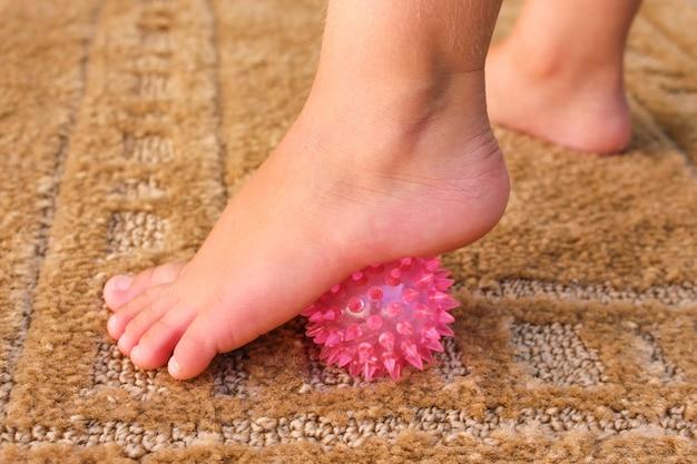 Crianças faz exercício para bola de massagem nos pés