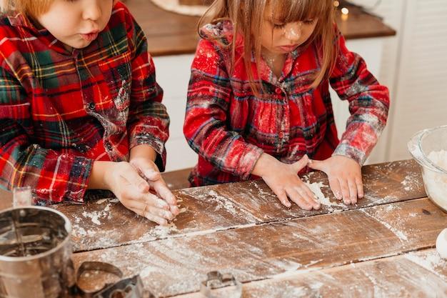 Crianças fazendo biscoitos de natal juntas