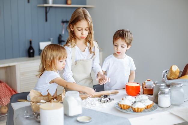 Crianças fazendo biscoitos na cozinha.