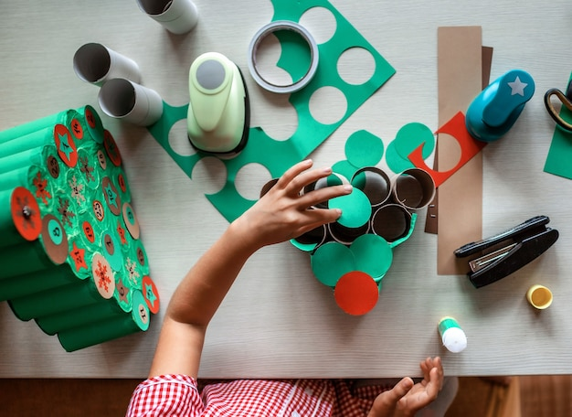Crianças fazendo calendário natalino feito à mão com rolos de papel higiênico em casa