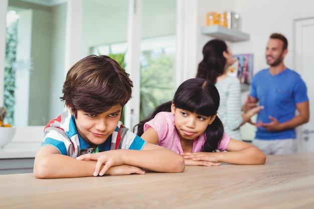 Crianças fazendo caretas enquanto está sentado na mesa