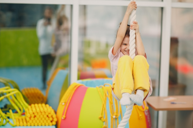 Crianças fazendo exercícios de escalada na corda bamba no ginásio, no jardim de infância ou na escola primária. conceito de esporte e fitness de crianças.