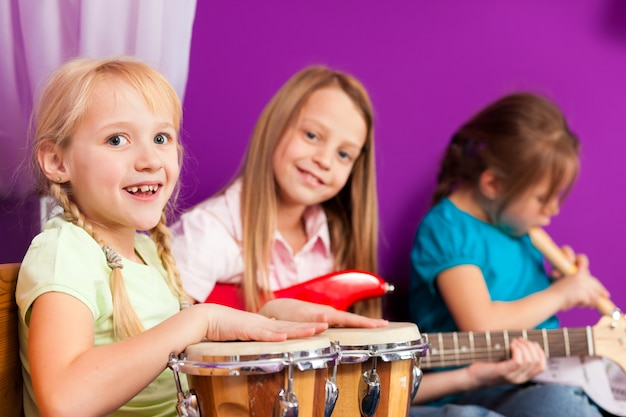 Crianças fazendo música com instrumentos em casa