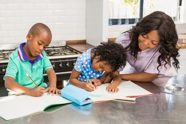 Crianças fazendo o dever de casa com a mãe
