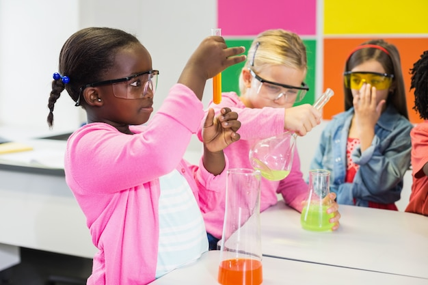 Crianças fazendo um experimento químico em laboratório