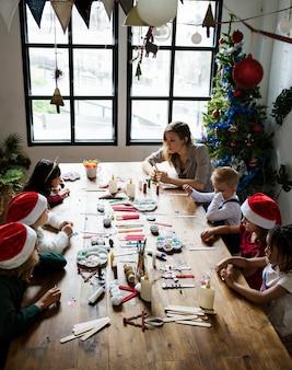 Crianças fazendo um projeto de natal diy