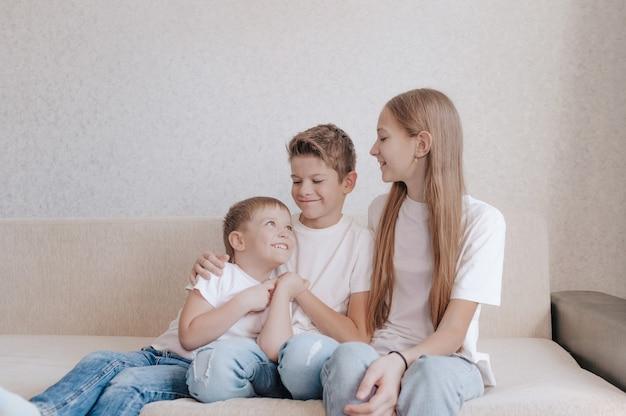 Crianças felizes amigáveis, uma menina e dois meninos estão sentados no sofá, sorrindo e olhando um para o outro.