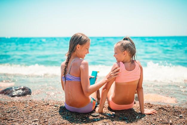 Crianças felizes aplicando protetor solar umas nas outras na praia. o conceito de proteção contra radiação ultravioleta