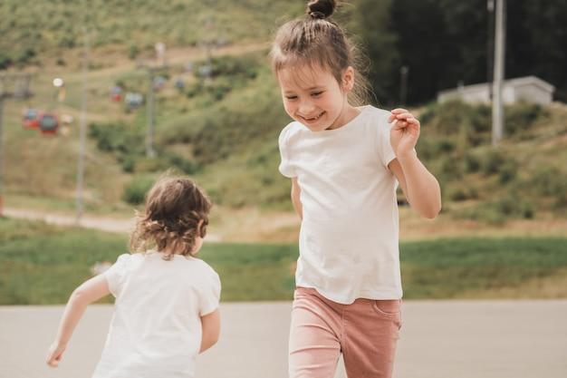 Crianças felizes aproveitam a vida e dançam crianças em camisetas brancas correm e brincam umas com as outras uma alegre ...