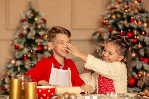 Crianças felizes assam biscoitos de gengibre para o natal