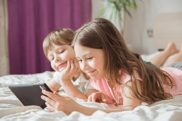 Crianças felizes assistindo a filmes online com ttablet digital e deitadas na cama em casa