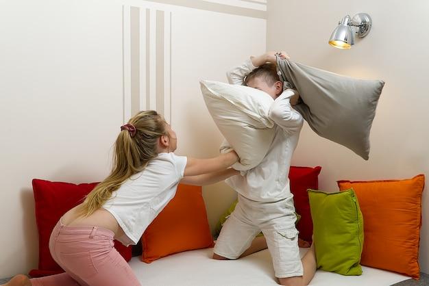 Crianças felizes, brigando com almofadas no quarto.
