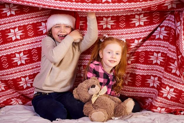 Crianças felizes brincam na cama sob uma manta vermelha.