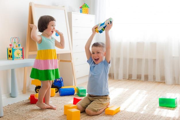 Crianças felizes brincam na sala no chão. irmão e irmã brincam juntos.