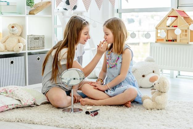 Crianças felizes brincando com batom de maquiagem