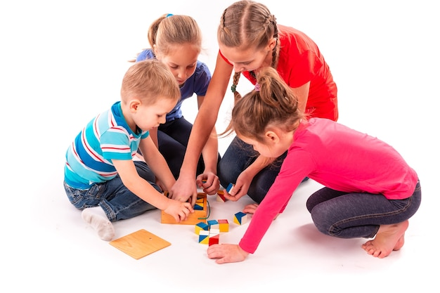 Crianças felizes brincando com blocos de construção isolados no branco. trabalho em equipe, conceito de criatividade.
