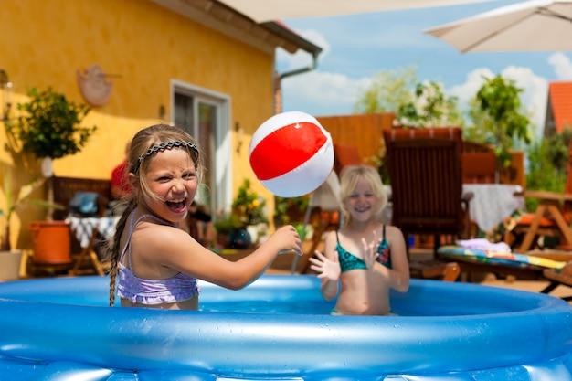 Crianças felizes brincando com bola na piscina