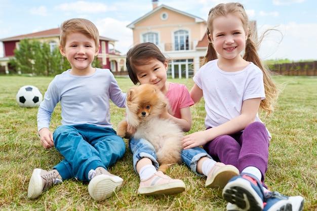 Crianças felizes brincando com cachorro