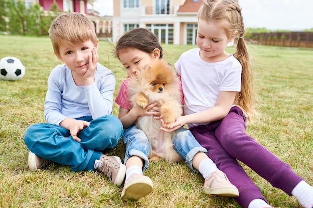 Crianças felizes brincando com filhote de cachorro bonito